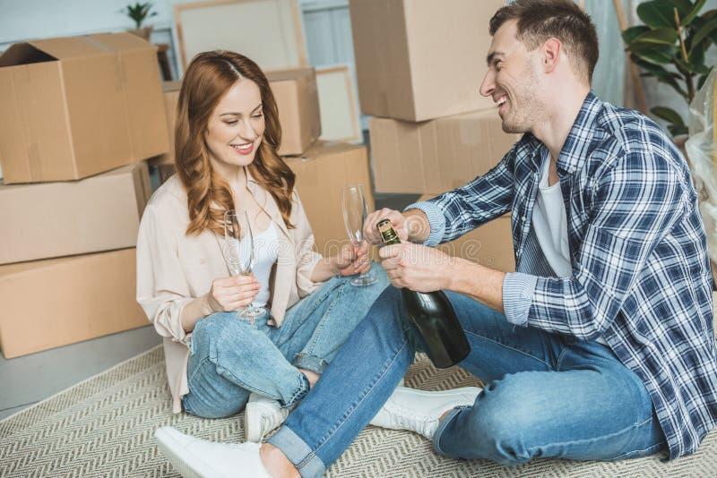 giovani coppie felici che celebrano rilocazione con champagne mentre sedendosi vicino alle scatole di cartone immagine stock