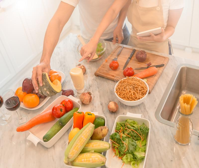 Giovani coppie felici che cucinano insieme nella cucina a casa esaminando il pc della compressa immagini stock