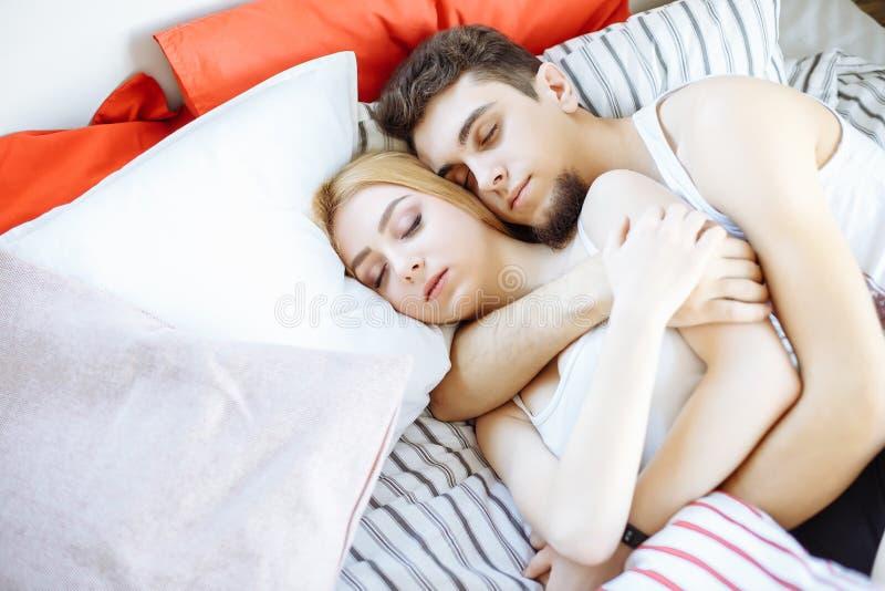 Giovani coppie felici che dormono a letto di mattina e concetto abbracciare, di amore e di relazioni fotografia stock