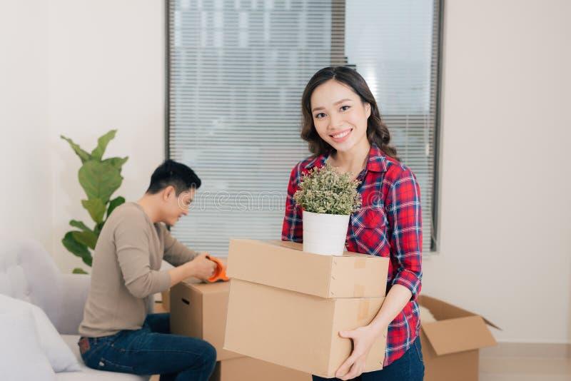 Giovani coppie felici che entrano nel nuovo appartamento con boxe d'imballaggio fotografia stock libera da diritti