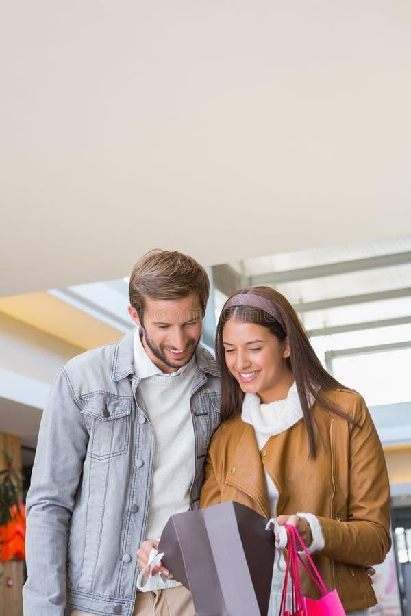 Giovani coppie felici che esaminano i sacchetti della spesa fotografia stock libera da diritti