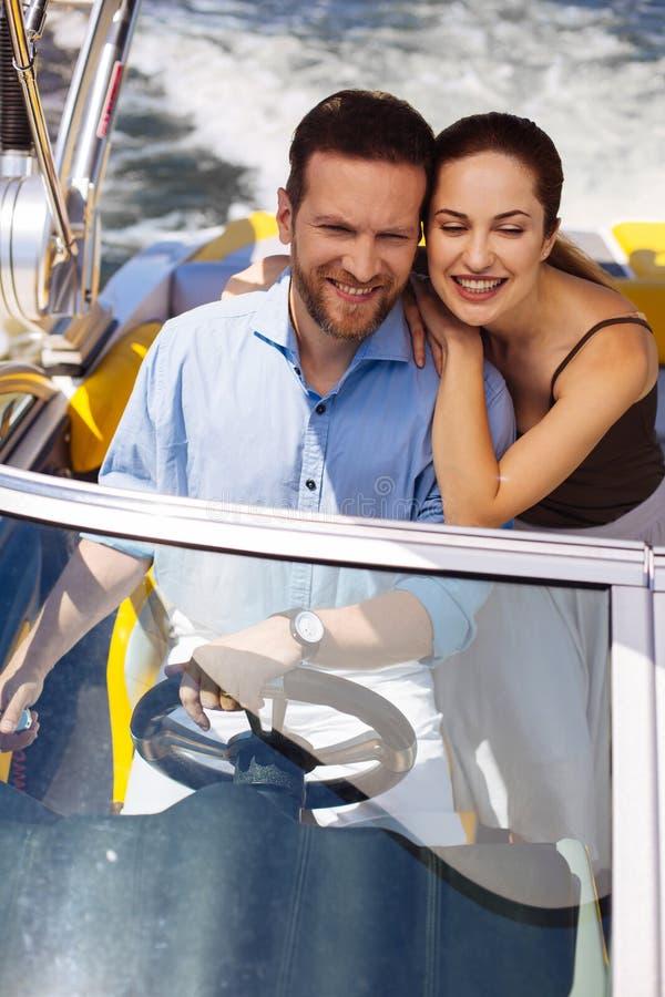 Giovani coppie felici che godono del giro sul loro yacht fotografia stock libera da diritti