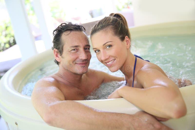 Giovani coppie felici che godono della stazione termale immagini stock