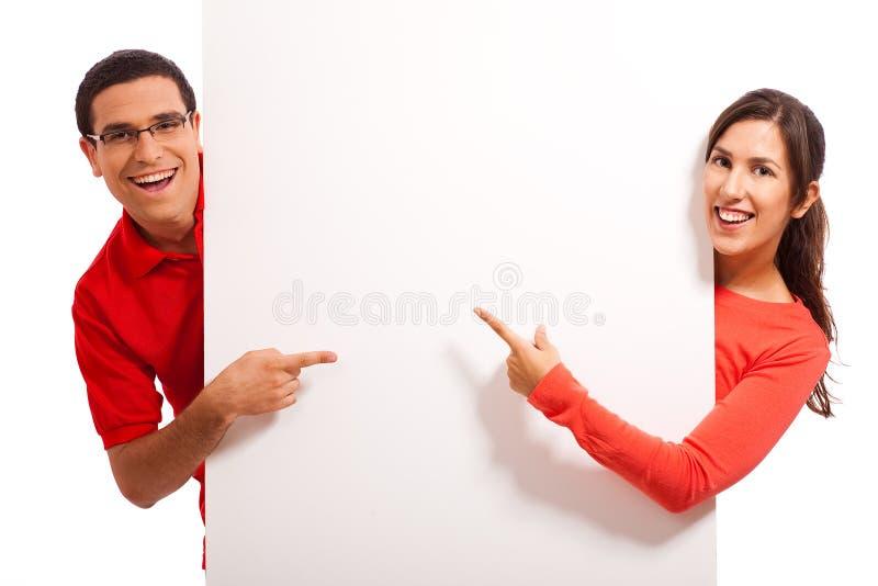 Giovani coppie felici che indicano lo spazio della copia fotografie stock