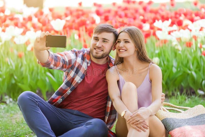 Giovani coppie felici che prendono selfie in parco il giorno di molla immagini stock libere da diritti