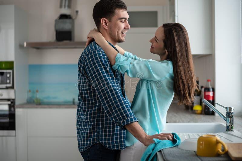 Giovani coppie felici che se abbracciano e che esaminano all'interno di nuova cucina, felicità in una nuova casa fotografie stock