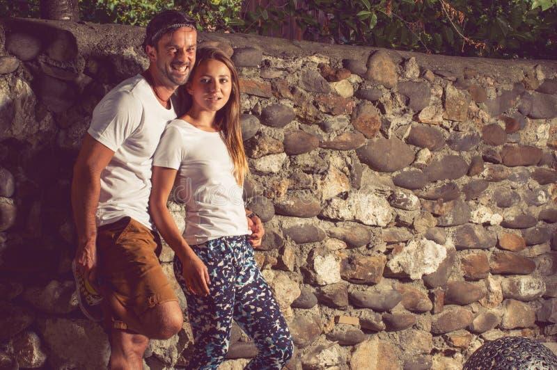 Giovani coppie felici che si siedono parete di pietra vicina all'aperto fotografia stock