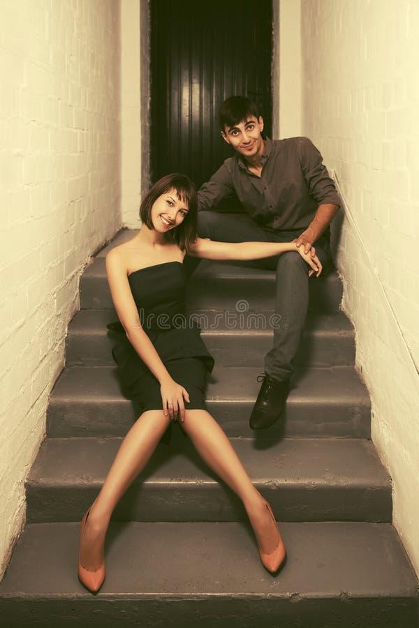 Giovani coppie felici che si siedono sui punti all'appartamento immagini stock
