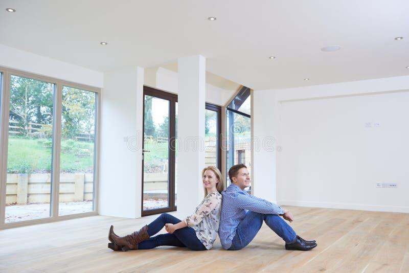Giovani coppie felici che si siedono sul pavimento nella nuova casa immagini stock libere da diritti
