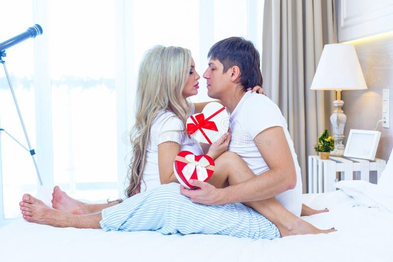 Giovani coppie felici che si trovano a letto, busta ispana del presente di sorpresa della donna di elasticità dell'uomo con il na fotografie stock