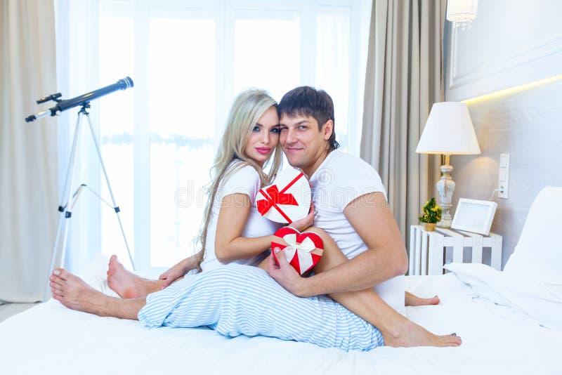 Giovani coppie felici che si trovano a letto, busta ispana del presente di sorpresa della donna di elasticità dell'uomo con il na fotografia stock libera da diritti