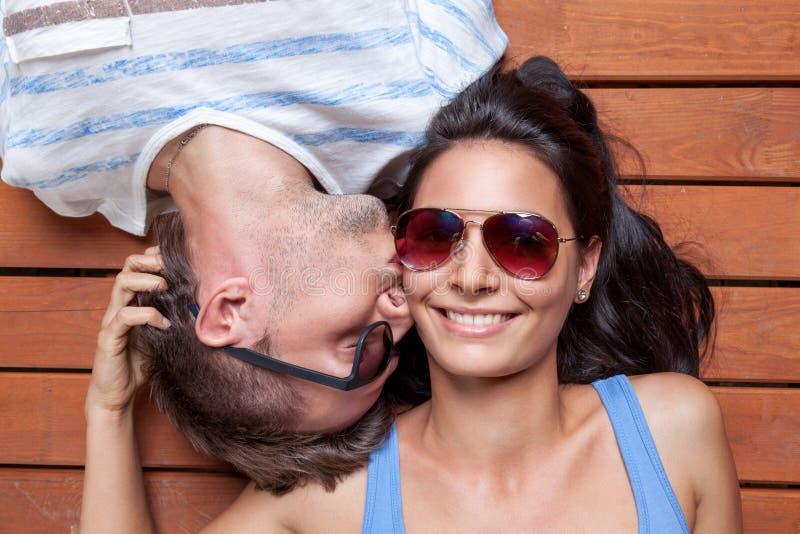Giovani coppie felici che si trovano su un pavimento di legno fotografie stock