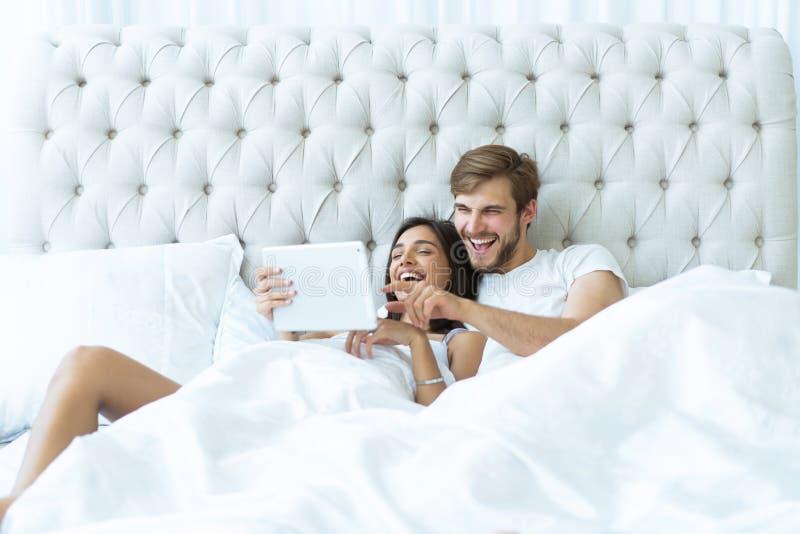 Giovani coppie felici che si trovano sul letto in una camera da letto e che per mezzo della compressa digitale fotografia stock