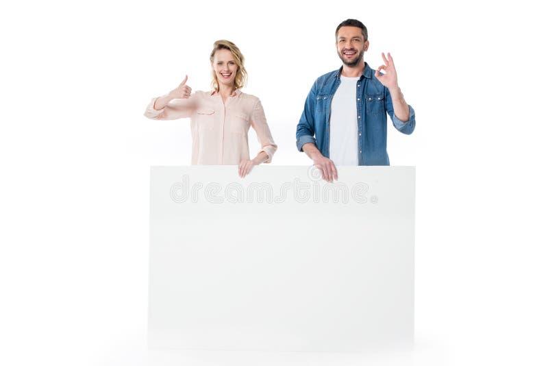 Giovani coppie felici che tengono insegna in bianco e che gesturing riuscito segno immagine stock libera da diritti