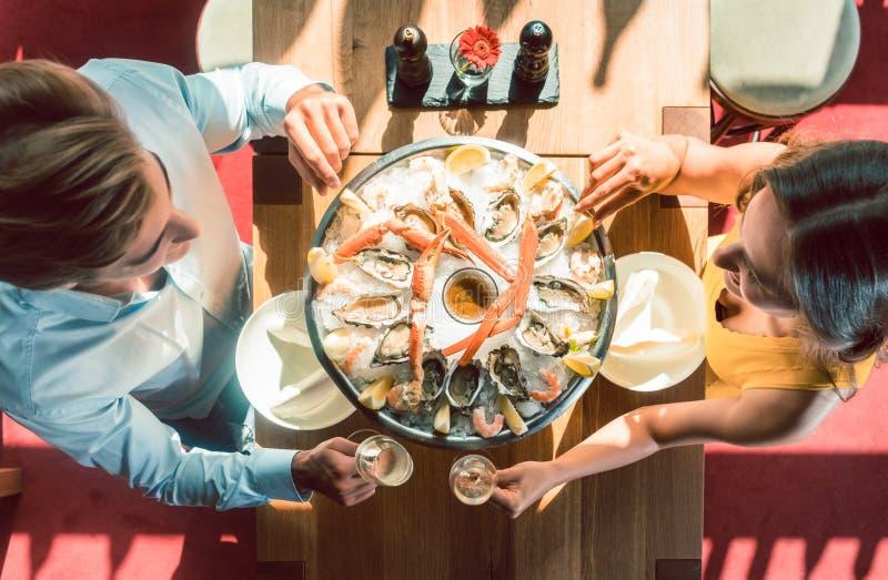 Giovani coppie felici che tostano durante la cena romantica ad un ristorante d'avanguardia immagini stock