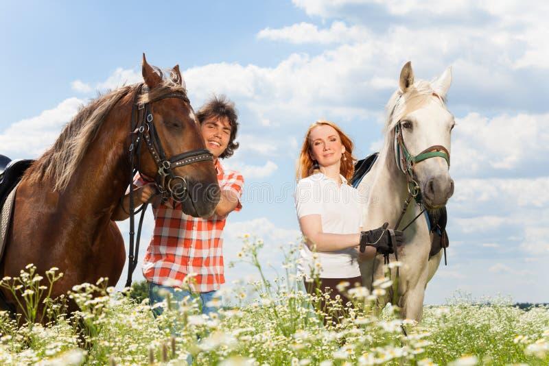 Giovani coppie felici con i loro cavalli di razza fotografia stock