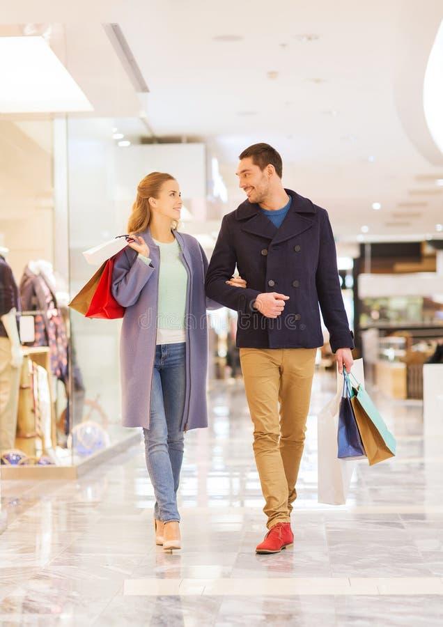 Giovani coppie felici con i sacchetti della spesa in centro commerciale immagine stock
