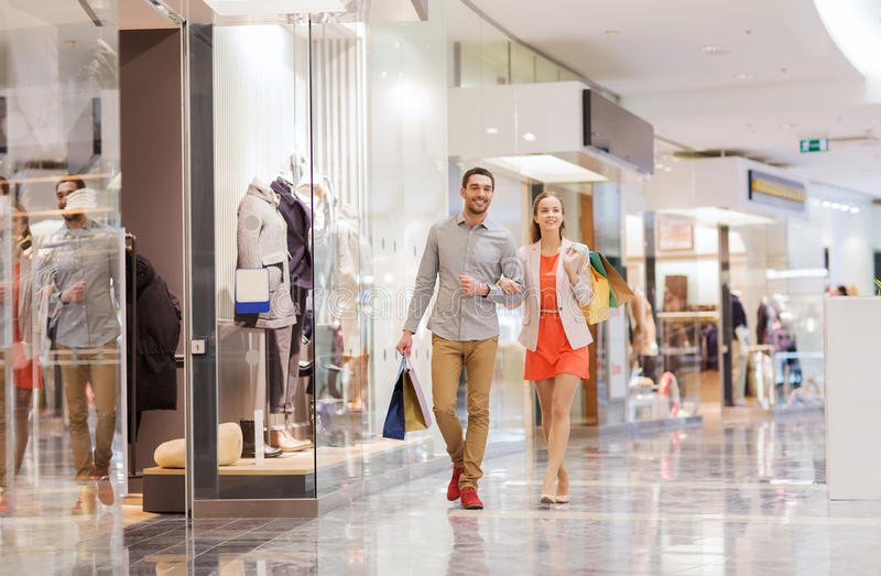 Giovani coppie felici con i sacchetti della spesa in centro commerciale fotografia stock