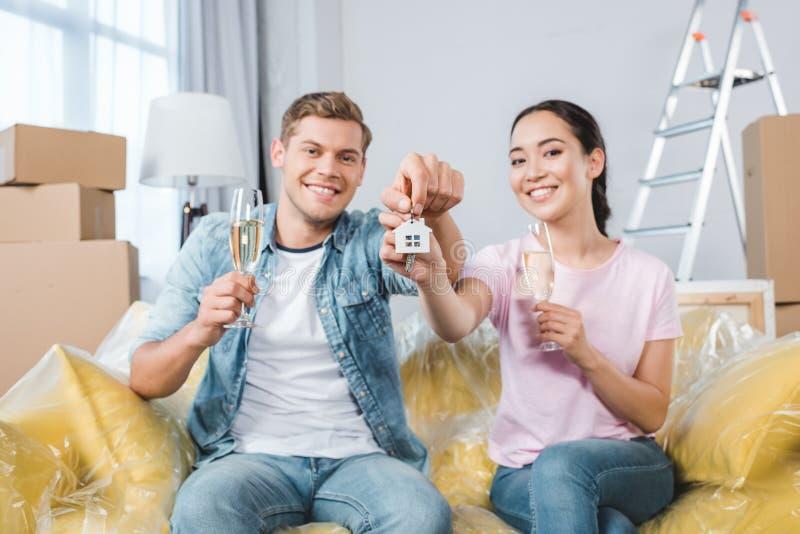 giovani coppie felici con i vetri di champagne e delle chiavi che si siedono sullo strato dopo la rilocazione in fotografie stock