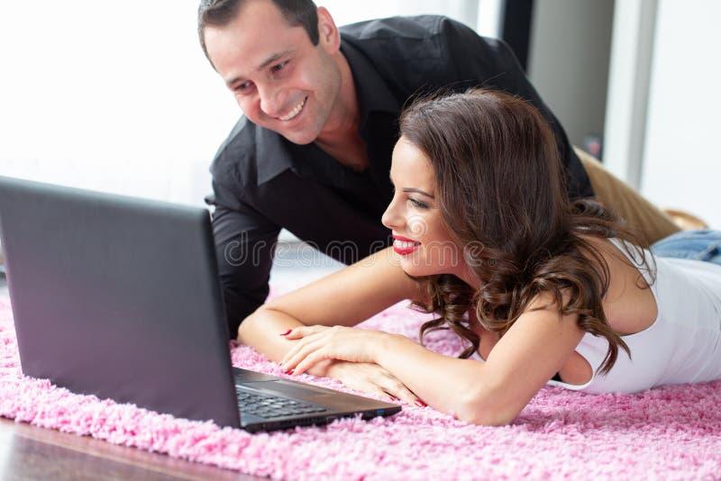 Giovani coppie felici con il computer portatile su tappeto immagini stock
