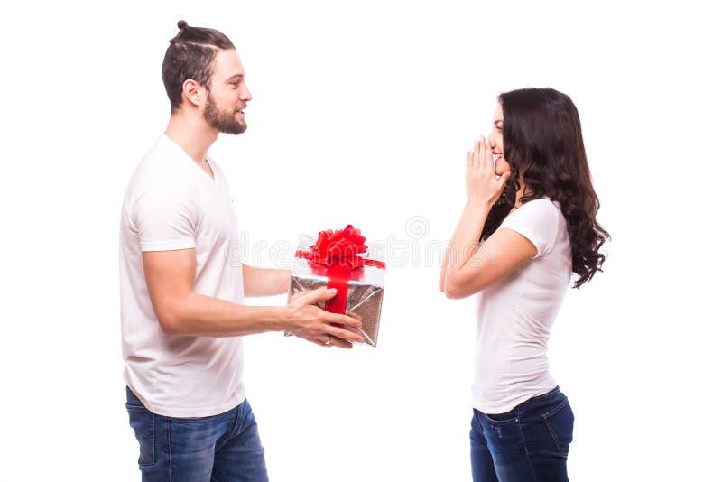 Giovani coppie felici con il presente di San Valentino isolato su un fondo bianco immagini stock