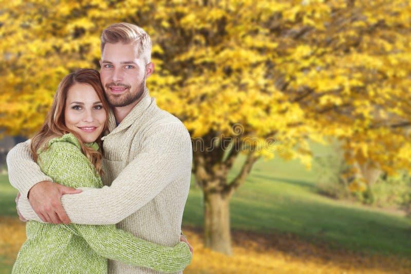 Giovani coppie felici davanti al fondo di caduta fotografia stock libera da diritti