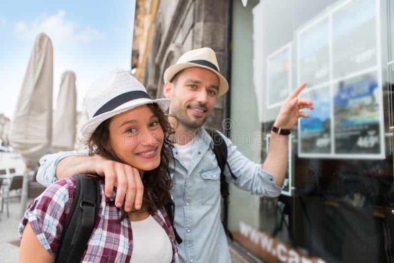 Giovani coppie felici davanti all'agenzia di viaggi immagini stock