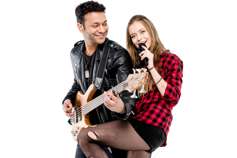 Giovani coppie felici dei musicisti con il microfono e la chitarra elettrica che eseguono insieme musica fotografia stock