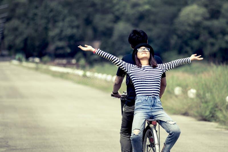 Giovani coppie felici dei pantaloni a vita bassa che guidano insieme una bicicletta fotografia stock