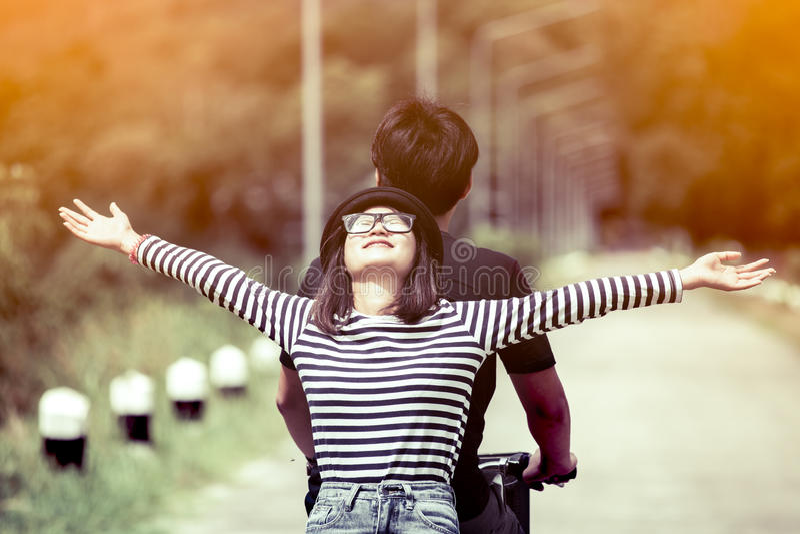 Giovani coppie felici dei pantaloni a vita bassa che guidano un togetherp della bicicletta fotografia stock