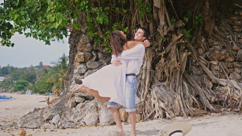 Giovani coppie felici divertendosi filando intorno abbracciare sulla spiaggia tropicale fotografie stock libere da diritti