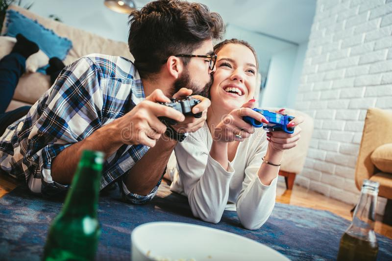 Giovani coppie felici divertendosi giocando i videogiochi immagine stock libera da diritti
