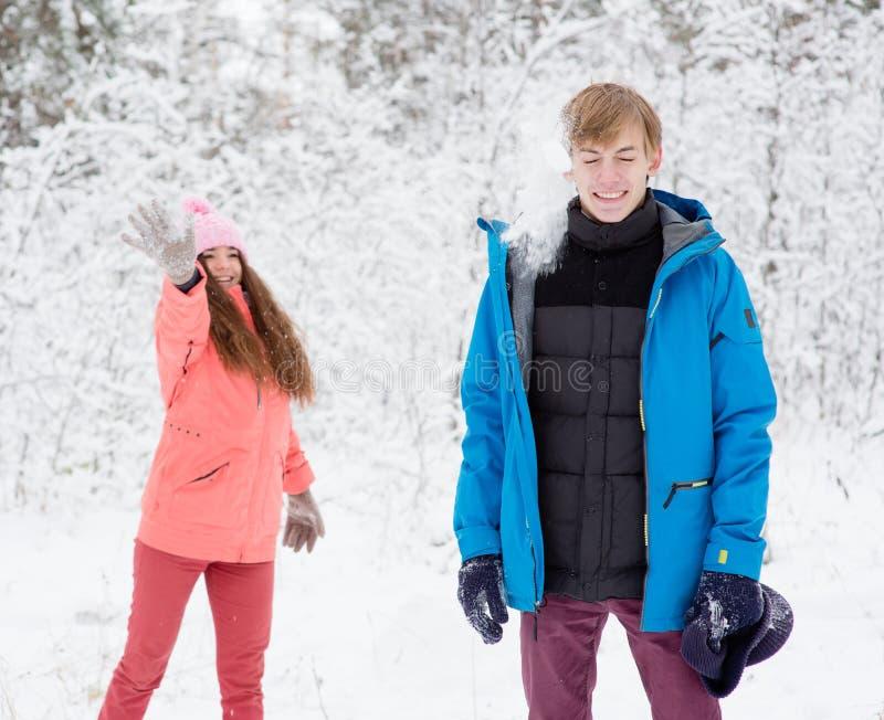 Giovani coppie felici divertendosi insieme nella neve nel terreno boscoso di inverno fotografia stock libera da diritti