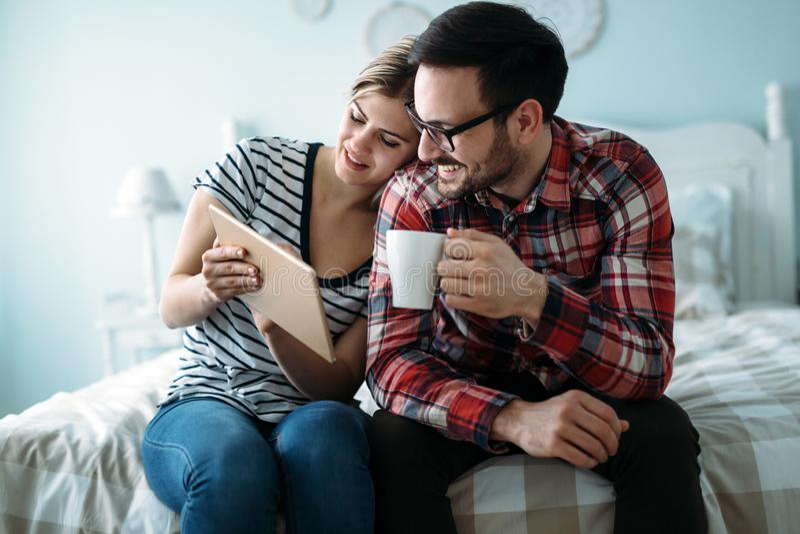 Giovani coppie felici facendo uso della compressa in camera da letto fotografie stock libere da diritti