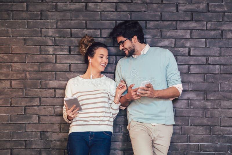 Giovani coppie felici facendo uso di una compressa e di uno Smart Phone su un muro di mattoni fotografia stock libera da diritti