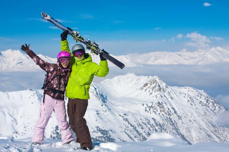 Giovani coppie felici in montagne di inverno fotografia stock libera da diritti