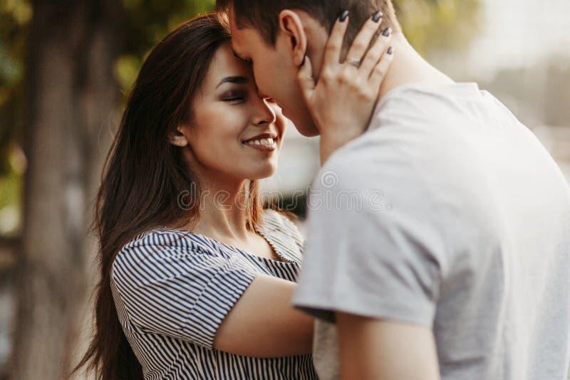 Giovani coppie felici negli amici degli adolescenti di amore vestiti nello stile casuale che bacia alla via fotografia stock