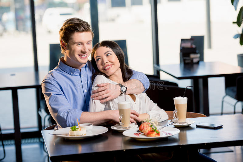 Giovani coppie felici nell'amore alla data romantica in ristorante fotografia stock