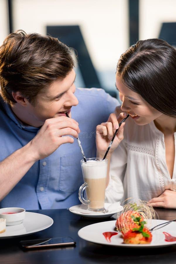 Giovani coppie felici nell'amore alla data romantica in ristorante immagine stock