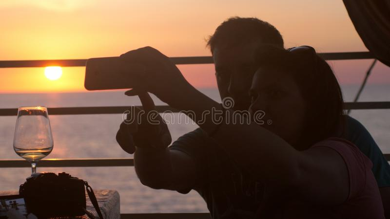 Giovani coppie felici nell'amore che prende la foto del selfie con il cellulare in caffè della spiaggia durante il bello tramonto fotografia stock libera da diritti