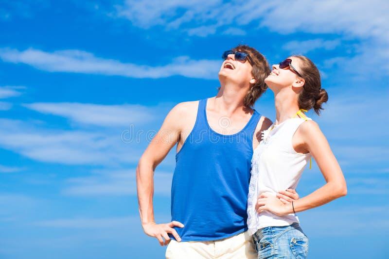 Giovani coppie felici nell'indicare sorridente degli occhiali da sole fotografia stock libera da diritti