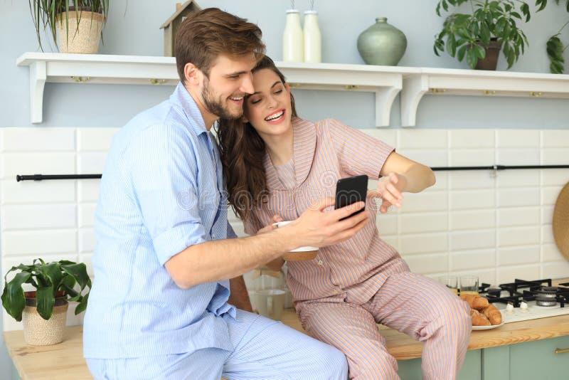 Giovani coppie felici in pigiami che guardano contenuto online in uno Smart Phone e che sorridono mentre cucinando nella cucina a fotografia stock libera da diritti