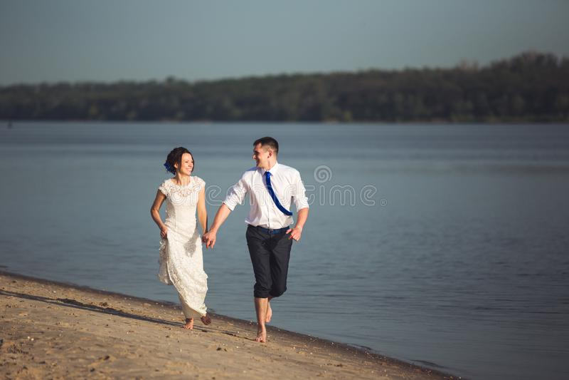Giovani coppie felici sensuali che celebrano il loro amore sulla spiaggia e sul divertiresi Immagine tonificata fotografie stock