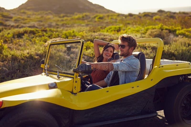 Giovani coppie felici su un viaggio stradale in automobile fotografia stock