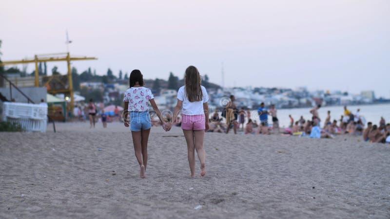 Giovani coppie femminili che si tengono per mano sulla spiaggia nella sera, due ragazze che camminano spiaggia, mare dei turisti fotografie stock