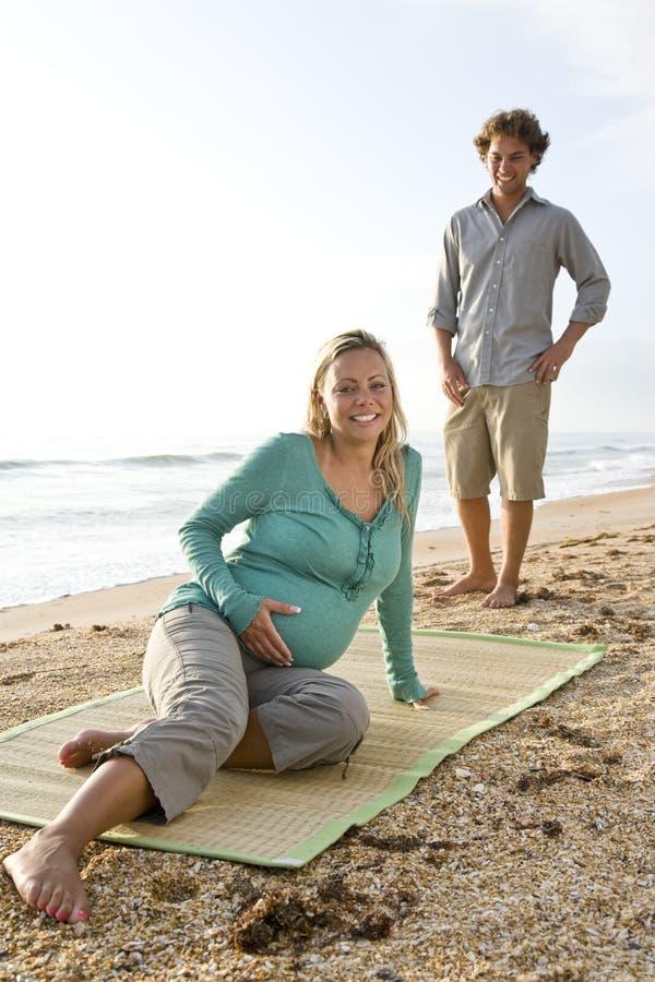 Giovani coppie incinte felici sulla sabbia alla spiaggia immagini stock libere da diritti