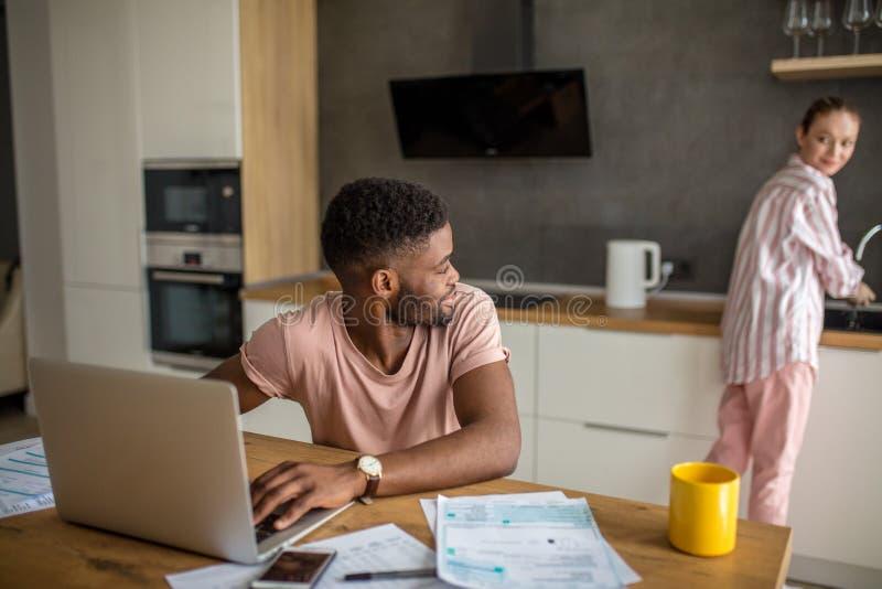 Giovani coppie interrazziali facendo uso del computer portatile insieme che mangia prima colazione a casa immagini stock libere da diritti