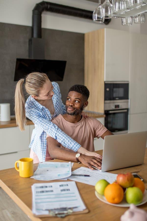 Giovani coppie interrazziali facendo uso del computer portatile insieme che mangia prima colazione a casa fotografia stock