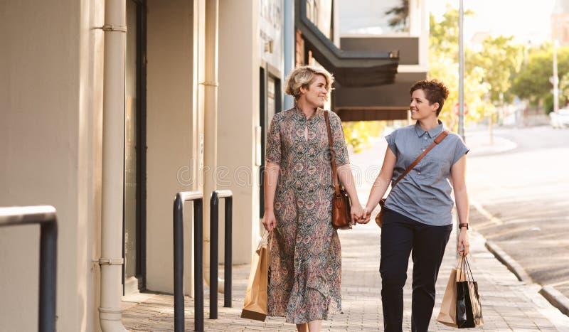 Giovani coppie lesbiche che camminano con i sacchetti della spesa nella città immagini stock