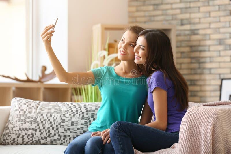 Giovani coppie lesbiche che prendono selfie a casa immagine stock libera da diritti